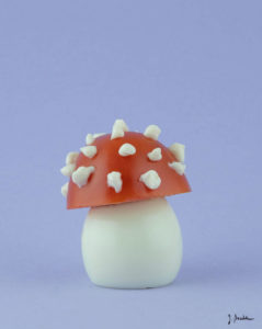 Ein Ei, eine halbe Tomate und Mayonaise formen einen Fliegenpilz.