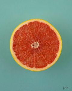 Eine aufgeshcnittene Grapefruit vor grünem Grund.