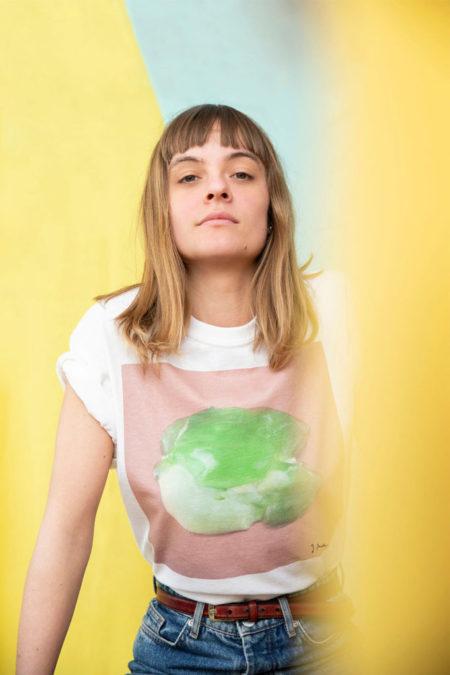 Eine Frau schaut in die Kamera und trägt ein T-Shirt mit einem Foto von Wackelpudding drauf.