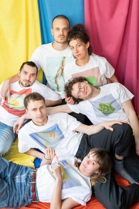 Sechs Personen sitzen vor einem bunten Hintergrund und tragen T-Shirts mit bunten Motiven.