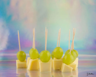 Käse-Trauben-Spieße stehen vor fluoreszierendem Hintergrund.
